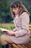 Kvinnor läser en bok i parkera Royaltyfria Bilder