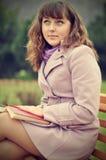 Kvinnor läser en bok i parkera Fotografering för Bildbyråer