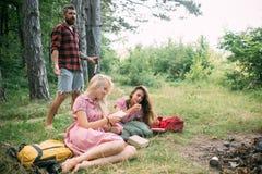 Kvinnor läste boken på lägereld Vänner kopplar av på brand Folk på brasan på grönt gräs Resa resväskan med seascapeinsida Campa arkivbilder