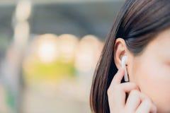 Kvinnor lyssnar till musik från vit hörlurar Och genom att använda handhandlag för att använda olika funktioner royaltyfria foton