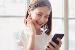 Kvinnor lyssnar till musik från vit hörlurar Och genom att använda handhandlag för att använda olika funktioner royaltyfri foto