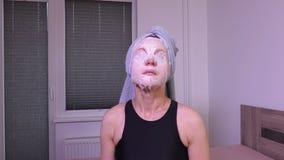 Kvinnor med den ansikts- maskeringen på framsidasammanträdet på säng stock video