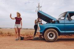 Kvinnor med den brutna ner bilen på vägtur Arkivfoto