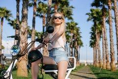 Kvinnor med den elektriska cykeln i parkera royaltyfri bild