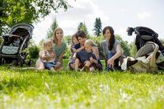 Kvinnor med deras barn som tycker om picknicken Royaltyfri Bild