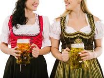 Kvinnor med dirndlen och Oktoberfest öl Royaltyfri Fotografi