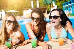 Kvinnor med drycker på sommar festar nära pölen royaltyfri bild