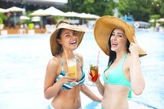 Kvinnor med drycker på sommar festar nära pölen royaltyfri foto