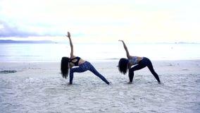 Kvinnor med ett spensligt diagram är förlovade i gymnastik på havet lager videofilmer