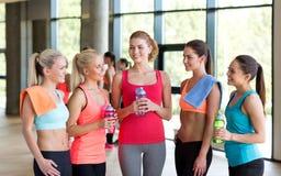 Kvinnor med flaskor av vatten i idrottshall fotografering för bildbyråer