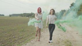 Kvinnor med kulör rök bombarderar att koppla av i natur
