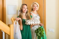 Kvinnor med matköp på ingången Arkivbilder