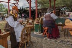Kvinnor med medeltida dräkter som arbetar med tyg Royaltyfria Foton