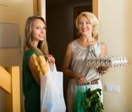 Kvinnor med påsar av mat nära dörr Royaltyfri Foto