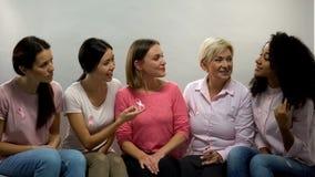 Kvinnor med rosa band som pratar, grupp av hälsa för servicebröstcancerpatienter fotografering för bildbyråer