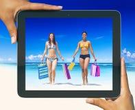 Kvinnor med shoppingpåsar på en tropisk strand Arkivfoto