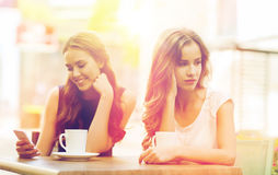 Kvinnor med smartphones och kaffe på det utomhus- kafét Royaltyfria Bilder