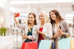 Kvinnor med smartphones som shoppar och tar selfie Arkivbild