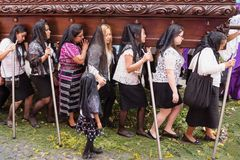 Kvinnor med svart skyler att gå över blommamatta och att bära en flöte på processionen av San Bartolome de Becerra, Antigua, Gua Fotografering för Bildbyråer