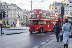Kvinnor med ulllaget korsar vägen framme av Trafalgar Square med London den röda bussen fotografering för bildbyråer