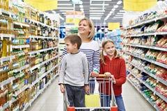 Kvinnor och barn med vagnsshopping i supermarket Royaltyfri Foto