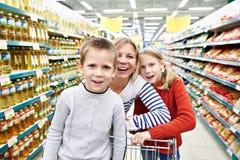 Kvinnor och barn med vagnsshopping i supermarket Arkivfoto