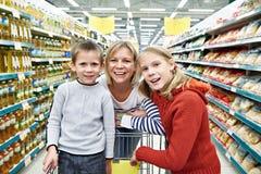 Kvinnor och barn med vagnsshopping i supermarket Arkivfoton