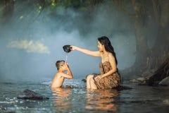 Kvinnor och barn som spelar strömmen Arkivbilder