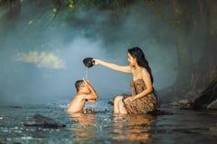 Kvinnor och barn som spelar strömmen Fotografering för Bildbyråer