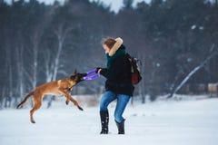 Kvinnor och belgisk herde Dog i vinter snowing för bakgrund Djupfryst skog arkivbilder