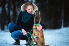 Kvinnor och belgisk herde Dog i vinter snowing för bakgrund Djupfryst skog royaltyfri bild