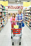 Kvinnor och flicka med vagnsshopping i supermarket Royaltyfri Foto