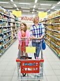 Kvinnor och flicka med vagnsshopping i supermarket Arkivfoto
