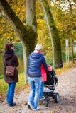 Kvinnor och flicka som går med en barnvagn till och med parkera arkivfoto