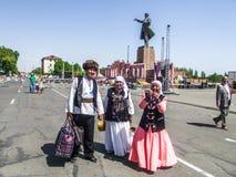 Kvinnor och män i den kirgiziska nationella klänningen Arkivbilder