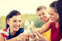 Kvinnor och män med drinkar på stranden Royaltyfri Foto