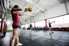 Kvinnor och män som övar i gymnastiksal Fotografering för Bildbyråer