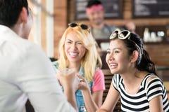 Kvinnor och man i asiatiskt kafé som dricker kaffe Fotografering för Bildbyråer