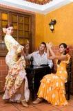Kvinnor och mannen i traditionella flamencoklänningar dansar under Feria de Abril på April Spain Arkivbilder