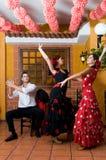 Kvinnor och mannen i traditionella flamencoklänningar dansar under Feria de Abril på April Spain Royaltyfri Bild