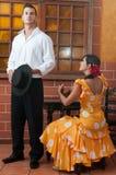 Kvinnor och mannen i traditionella flamencoklänningar dansar under Feria de Abril på April Spain Royaltyfria Bilder