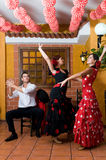 Kvinnor och mannen i traditionella flamencoklänningar dansar under Feria de Abril på April Spain Royaltyfri Bild