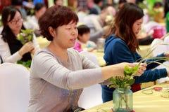 Kvinnor och ungar lär blom- ordningar Arkivbild