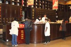 Kvinnor på arbete i en forntida farmacy i Hangzhou, Kina Arkivbild