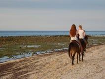 Kvinnor på hästryggridning på stranden Royaltyfria Foton
