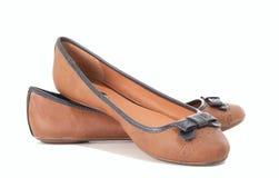 Kvinnor piskar skor på vit Arkivbilder