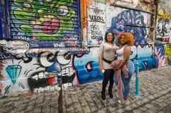 Kvinnor poserar framme av färgrika grafitti på Rue Denoyez i Paris Royaltyfri Bild
