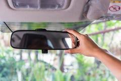 Kvinnor räcker att justera spegeln för den bakre sikten arkivbild
