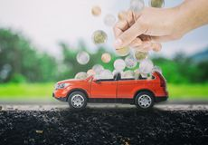 Kvinnor räcker att sätta mynt in i en röd bil för att fylla upp Begreppet av besparingen som köper den nya bilen Fotografering för Bildbyråer