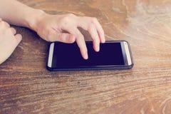 Kvinnor räcker genom att använda en smart telefon Arkivbilder